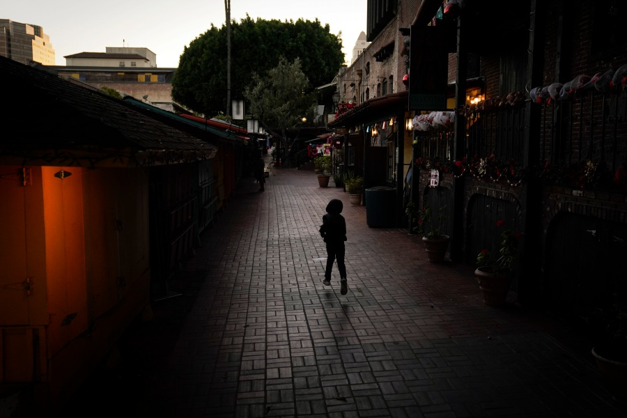 A boy chases a bird on an empty Olvera Street in downtown Los Angeles, Tuesday, Dec. 15, 2020. The tree-covered brick alley typically teeming with tourists is empty. Many of the shops that sell everything from traditional Mexican folk dresses to paintings of artist Frida Kahlo to sombreros are padlocked and the ones open have few, if any, customers. The strains of mariachi trios have fallen silent and the fragrance of taquitos frying has become less pungent. (Jae C. Hong / Associated Press)