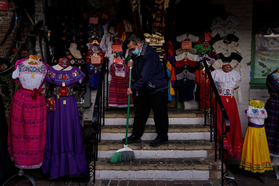 Victor Flores, 66, a third-generation owner of a gift shop, sweeps the steps of his store on Olvera Street in downtown Los Angeles on Dec. 16, 2020. (Jae C. Hong / Associated Press)
