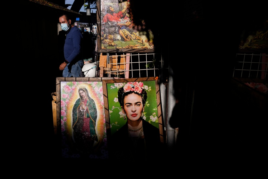 Framed paintings depicting Our Lady of Guadalupe and Mexican artist Frida Kahlo are placed outside a gift shop on Olvera Street in downtown Los Angeles, Wednesday, Dec. 16, 2020. The tree-covered brick alley typically teeming with tourists is empty. Many of the shops that sell everything from traditional Mexican folk dresses to paintings of artist Frida Kahlo to sombreros are padlocked and the ones open have few, if any, customers. (Jae C. Hong / Associated Press)