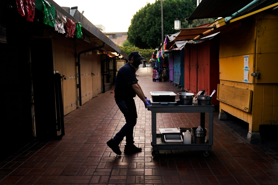 "Edward Flores, 56, a fourth-generation owner of Juanita's Cafe, pushes his cart through empty Olvera Street after closing his restaurant for the day in downtown Los Angeles, Wednesday, Dec. 16, 2020. ""It's pretty grim right now,"" said Flores. ""I know of six (businesses) that have gone belly up. These are my neighbors and my friends. To see them fail through no fault of their own is heartbreaking."" (AP Photo/Jae C. Hong)"
