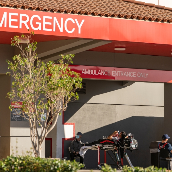 In this Dec. 18, 2020 file photo, an unidentified patient receives oxygen on a stretcher, while Los Angeles Fire Department Paramedics monitor him outside the Emergency entrance, waiting for admission at the CHA Hollywood Presbyterian Medical Center in Los Angeles. (AP Photo/Damian Dovarganes,File)