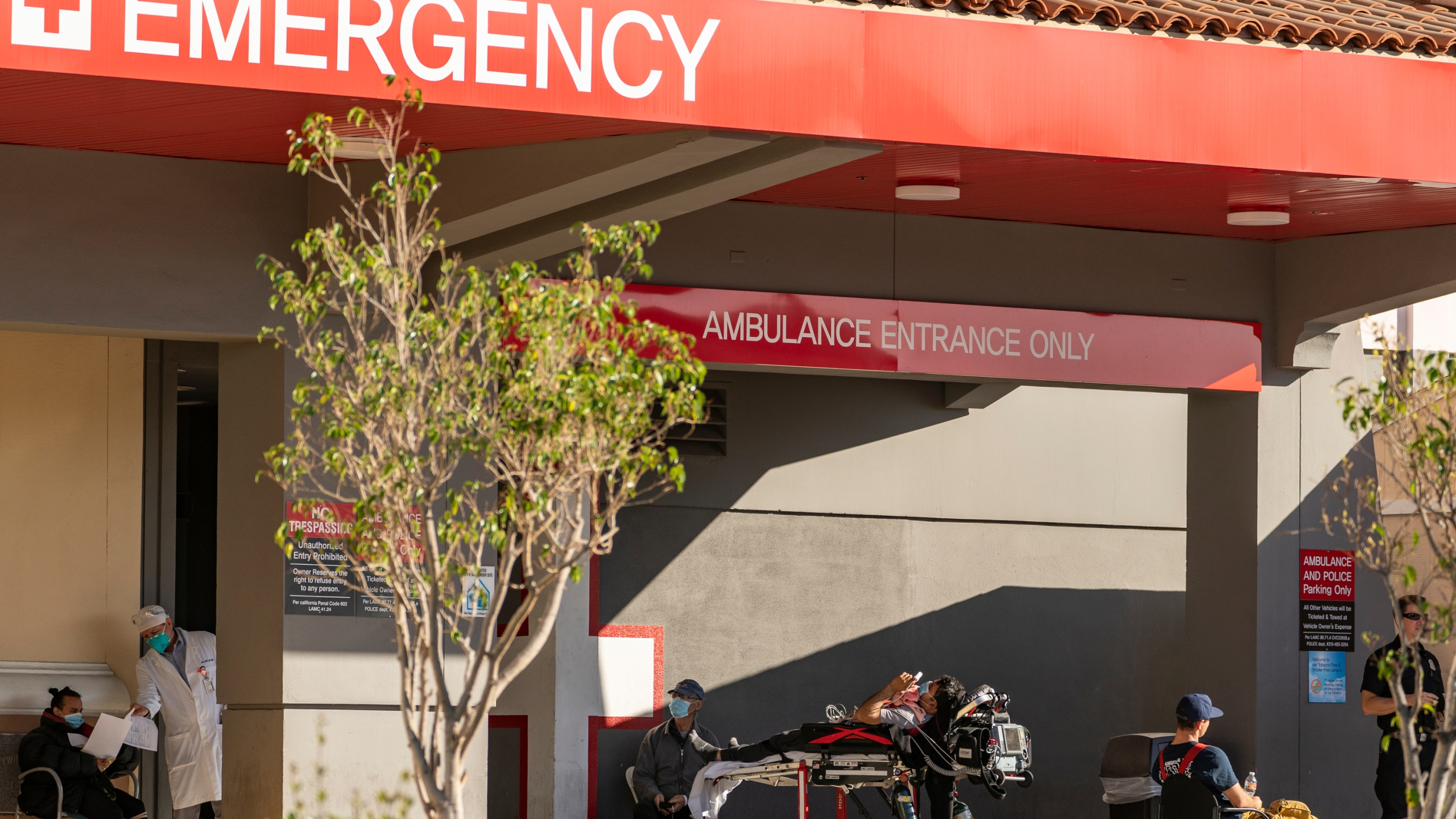 In this Dec. 18, 2020 file photo an unidentified patient receives oxygen on a stretcher, while Los Angeles Fire Department Paramedics monitor him outside the Emergency entrance, waiting for admission at the CHA Hollywood Presbyterian Medical Center in Los Angeles. (Damian Dovarganes/AP Photo)