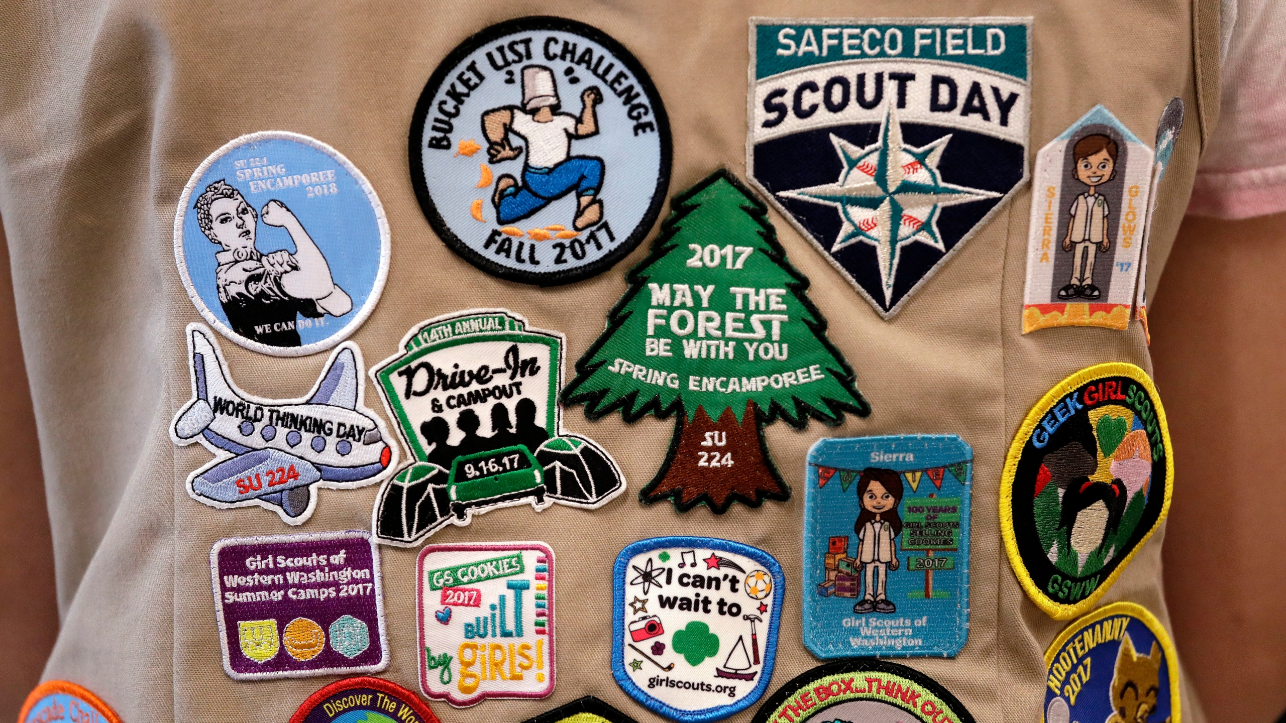 In this June 18, 2018, file photo, patches cover the back of a Girl Scout's vest at a demonstration of some of their activities in Seattle. (Elaine Thompson/AP Photo)