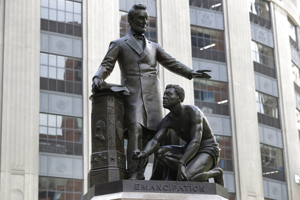 In this June 25, 2020, file photo, a statue that depicts a freed slave kneeling at President Abraham Lincoln's feet rests on a pedestal in Boston. On Tuesday, Dec. 29, the statue that drew objections amid a national reckoning with racial injustice was removed from its perch. (AP Photo/Steven Senne, File)