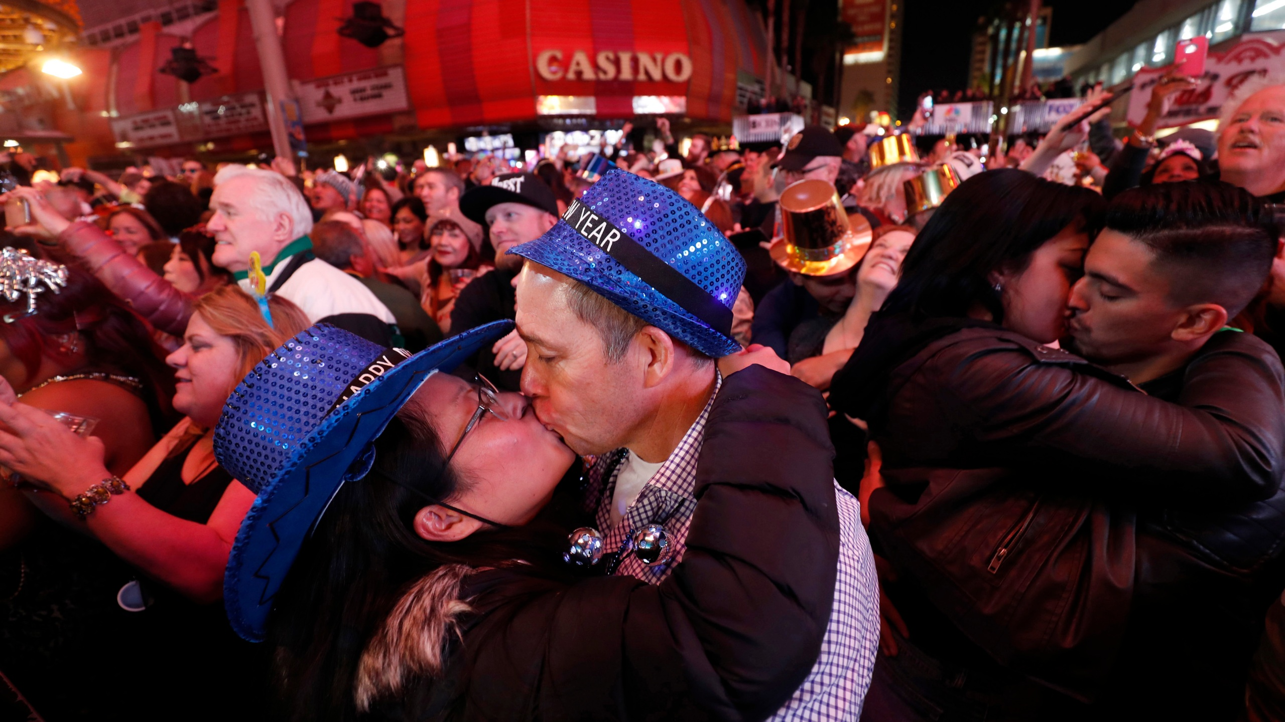 In this Jan. 1, 2018, file photo, newlyweds Alison and Kenny Finchum, lower left, of Tulsa, Okla., kiss just after midnight during a New Year's party at the Fremont Street Experience in downtown Las Vegas. (Steve Marcus/Las Vegas Sun via AP)