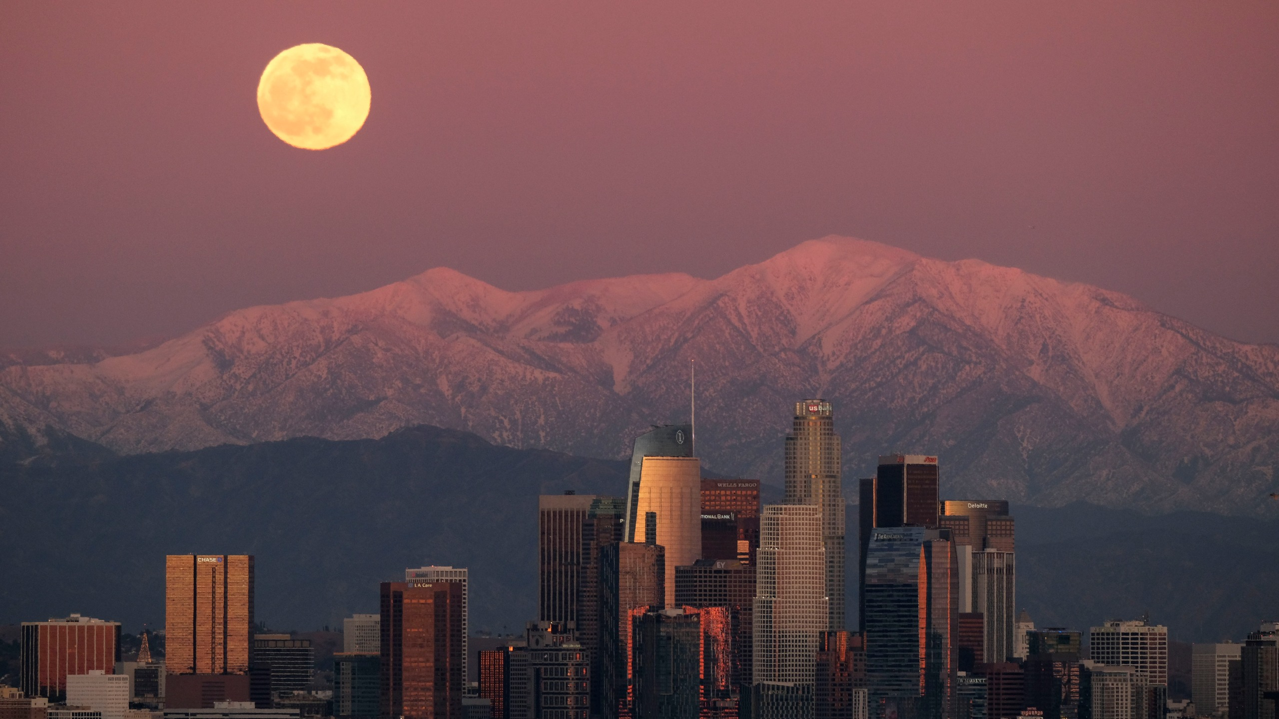 The moon rises over snow-covered mountains, behind the downtown Los Angeles skyline as seen from Kenneth Hahn State Recreation Area Tuesday, Dec. 29, 2020, in Los Angeles. (AP Photo/Ringo H.W. Chiu)