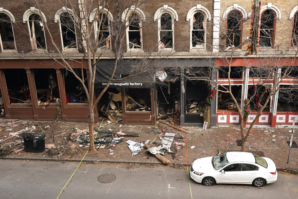 In this Dec. 29, 2020 file photo, debris remains on the sidewalk in front of buildings damaged in a Christmas Day explosion in Nashville, Tenn. (AP Photo/Mark Humphrey, File)