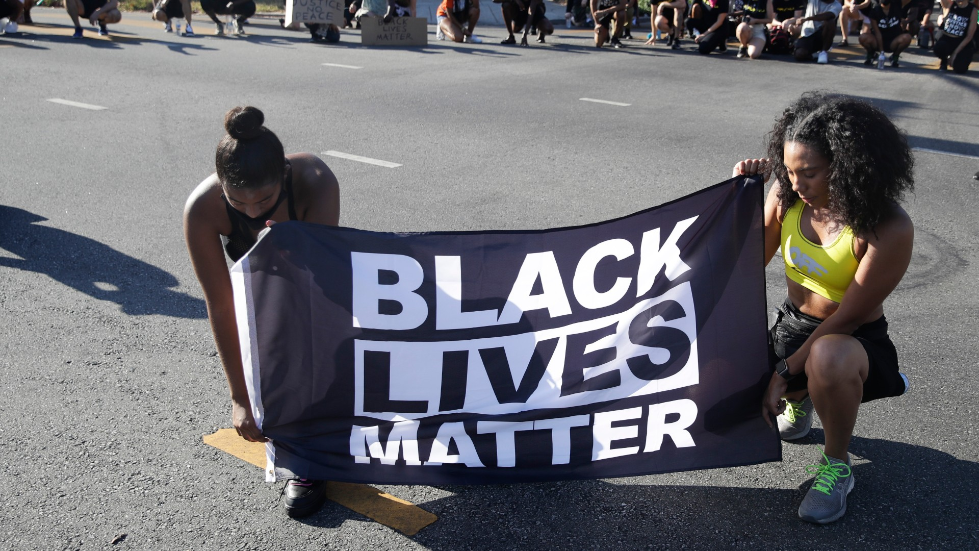 In this July 11, 2020 file photo, Alycia Pascual-Pena, left, and Marley Ralph kneel while holding a Black Lives Matter banner during a protest in memory of Breonna Taylor, in Los Angeles. Taylor was killed in her apartment by members of the Louisville, Ky., Metro Police Department on March 13. (AP Photo/Marcio Jose Sanchez, File)