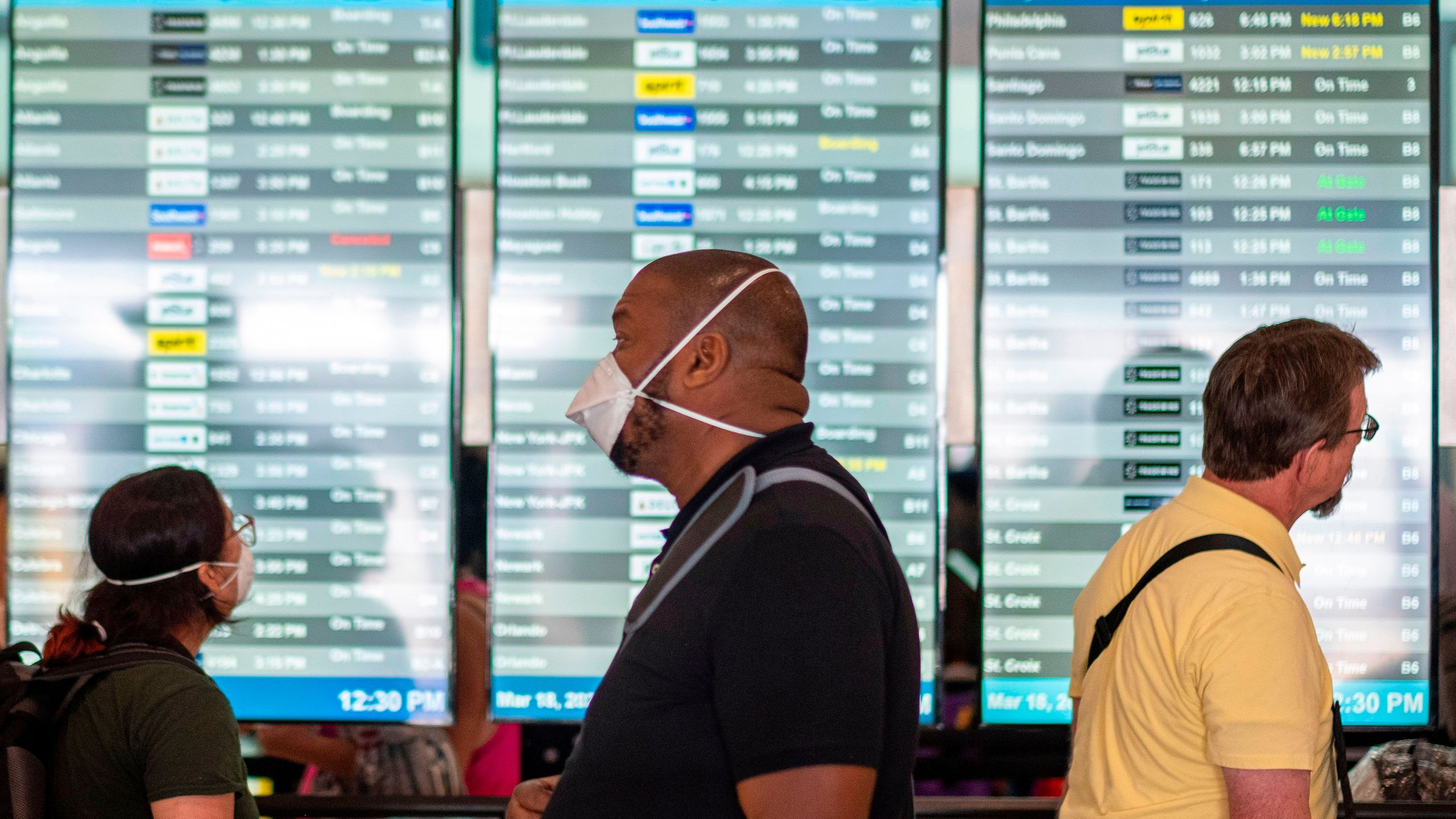 Travelers wearing masks wait in line at a security checkpoint at the Luis Munoz Marin International Airport in San Juan, Puerto Rico, on March 18, 2020. (Ricardo Arduengo / AFP / Getty Images)