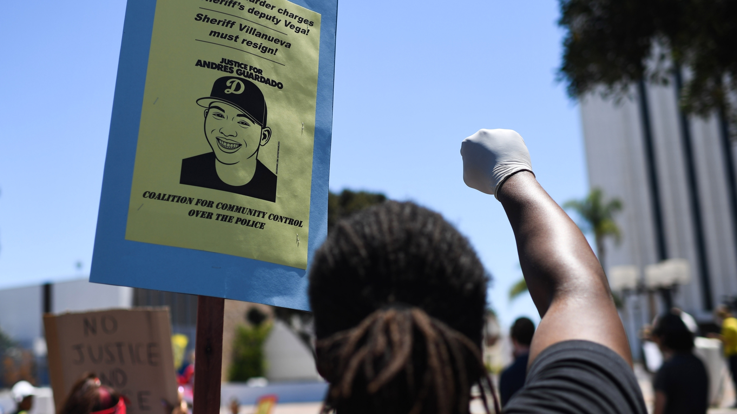 A person holds up a placard and a gloved fist during a protest in the Compton area calling for Los Angeles Sheriff's deputies to be held accountable for the shooting death of 18-year-old security guard Andres Guardado, on July 11, 2020. (ROBYN BECK/AFP via Getty Images)