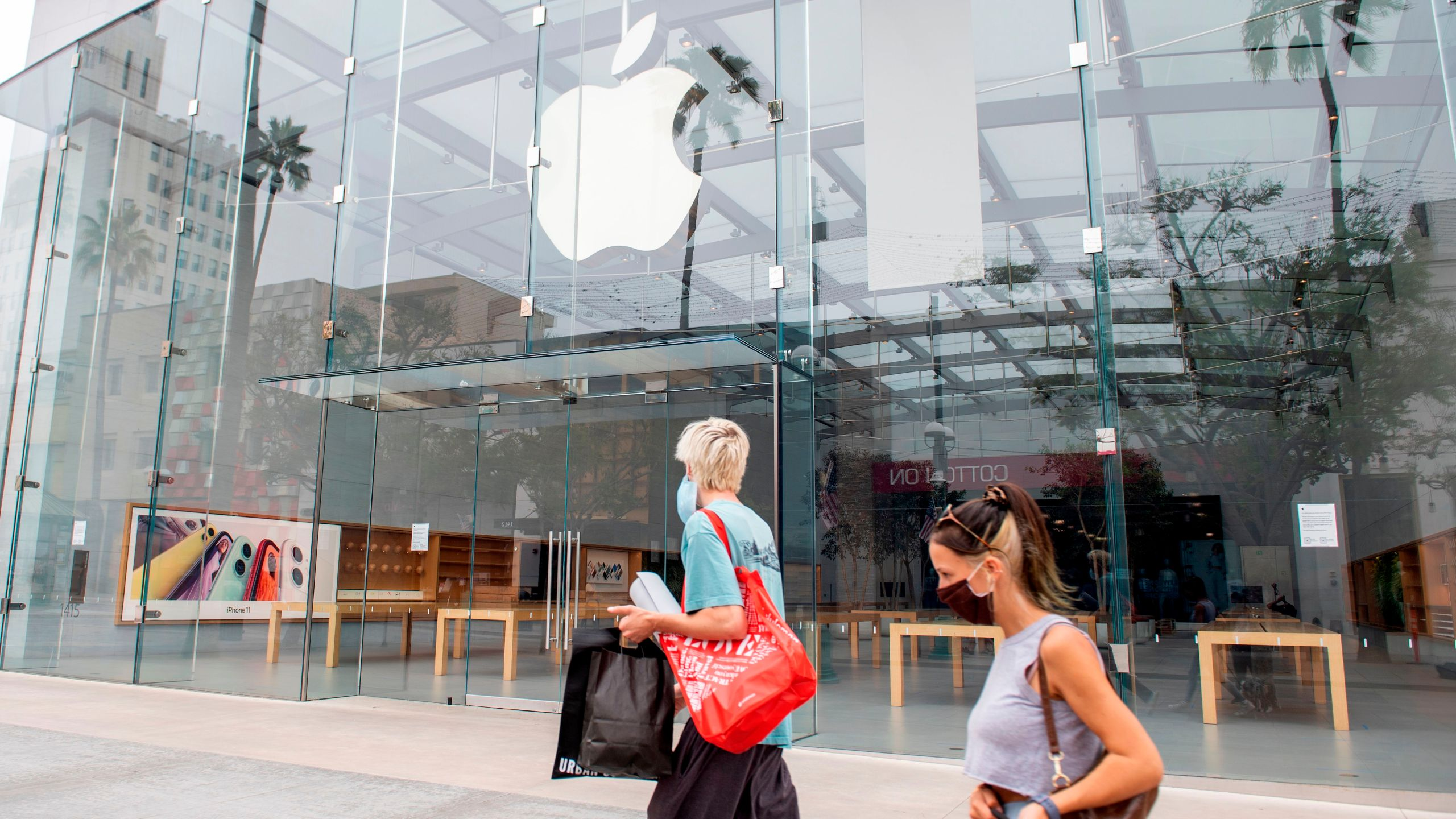 People wearing a mask walk by a closed Apple Store in Santa Monica, California, on July 28, 2020. (VALERIE MACON/AFP via Getty Images)
