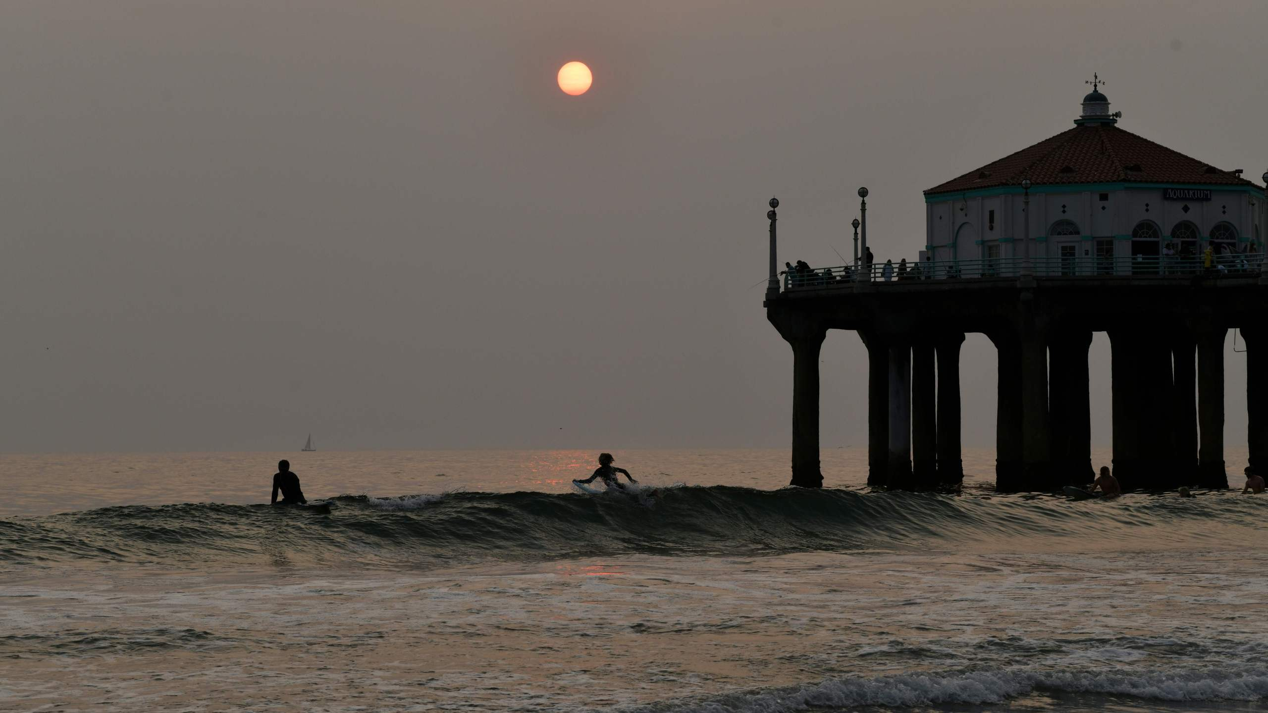 Surfers sit in the water at sunset during a heat wave on September 7, 2020 in Manhattan Beach, California. (Chris Delmas/AFP via Getty Images)