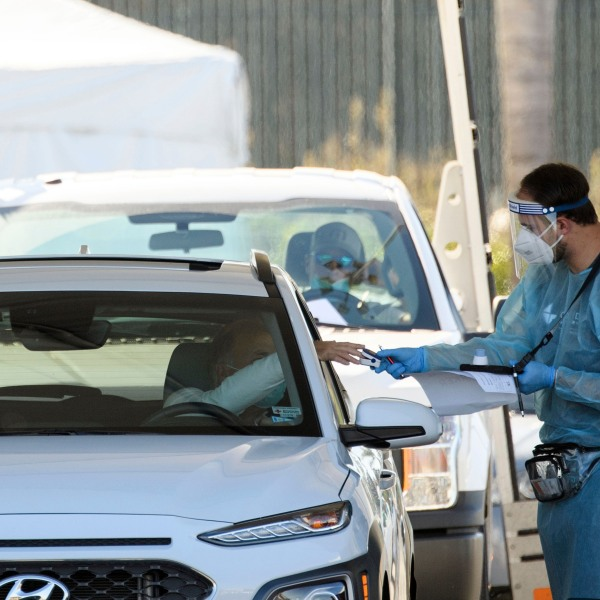 A COVID-19 testing site staff member uses a pulse oximeter to screen a driver at a drive-up testing site at the Orange County Fairgrounds in Costa Mesa on Nov. 17, 2020. (Patrick T. Fallon/AFP via Getty Images)