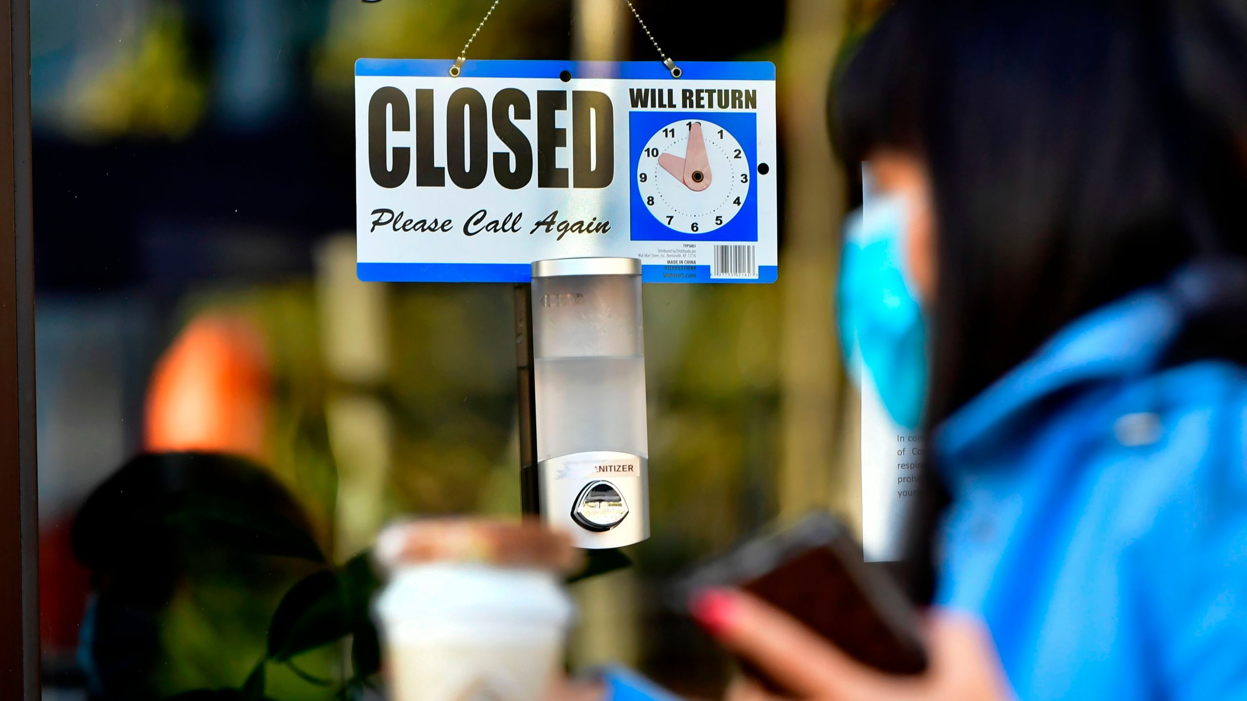 A pedestrian wearing her facemask and holding a cup of coffee walks past a 'closed' sign hanging on the door of a small business in Los Angeles on Nov. 30, 2020. (FREDERIC J. BROWN/AFP via Getty Images)