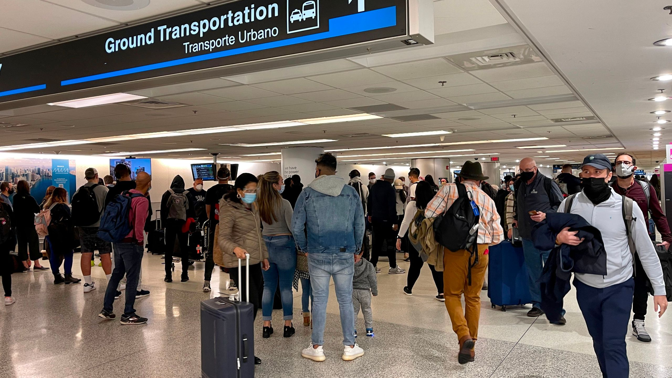 A crowd is seen, on Dec. 18, 2020 waiting by the baggage carousel at the Miami International Airport in Miami, Florida, as the Christmas holiday travel starts despite the coronavirus pandemic. (DANIEL SLIM/AFP via Getty Images)