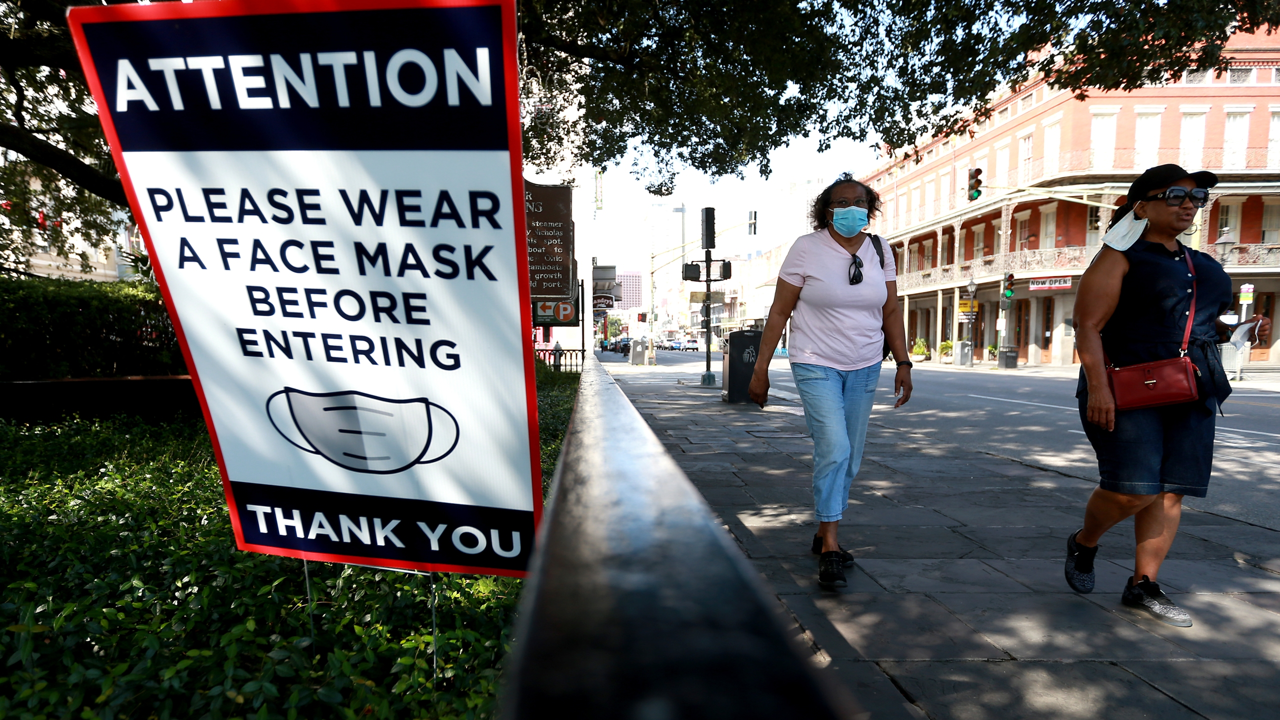 Visitors walk past face mask signs along Decatur Street in the French Quarter on July 14, 2020, in New Orleans, Louisiana. (Sean Gardner/Getty Images)