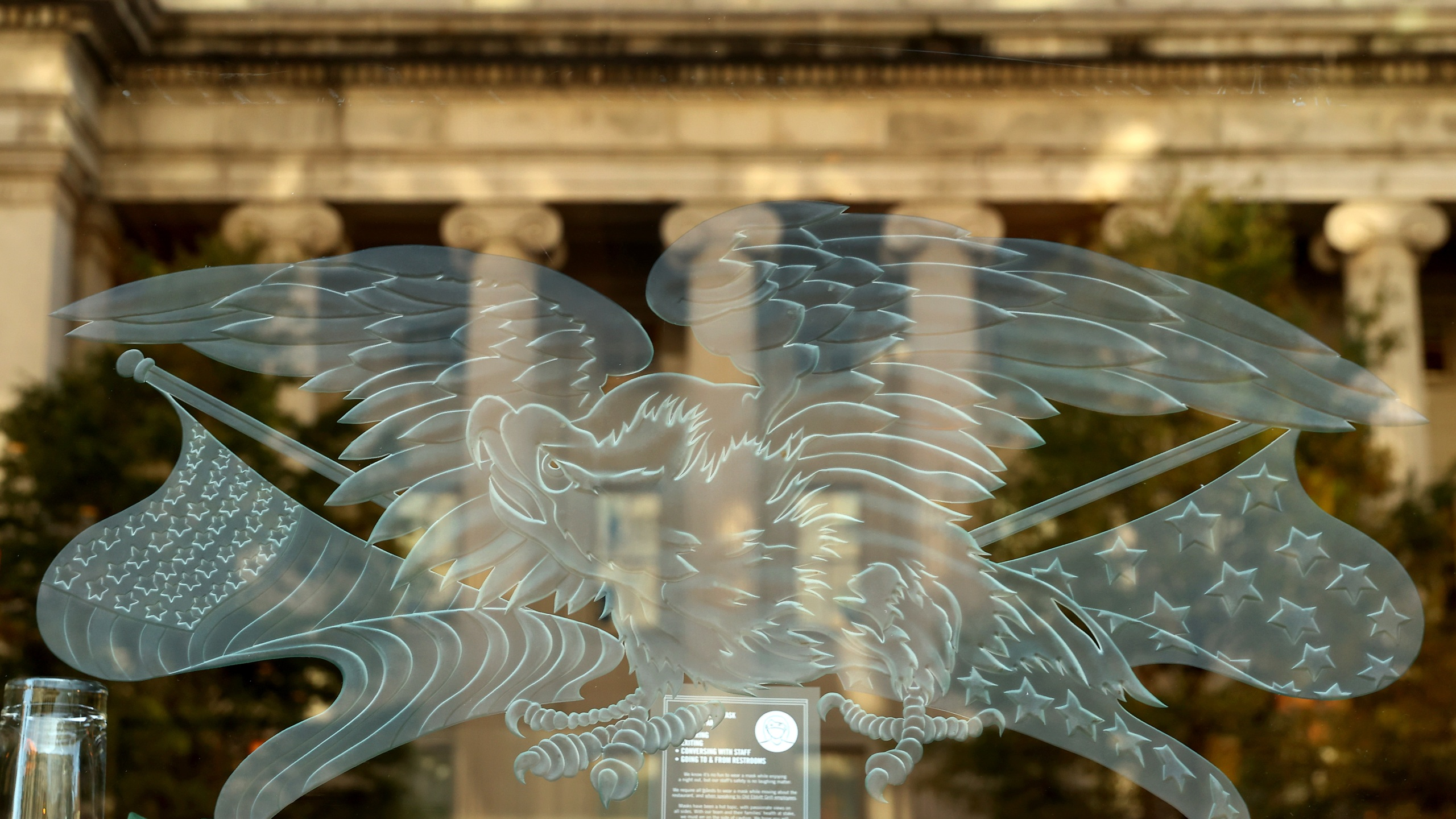 The U.S. Treasury Department is reflected in a restaurant window less than 24 hours before Election Day, on Nov. 2, 2020, in Washington, DC. (Chip Somodevilla/Getty Images)