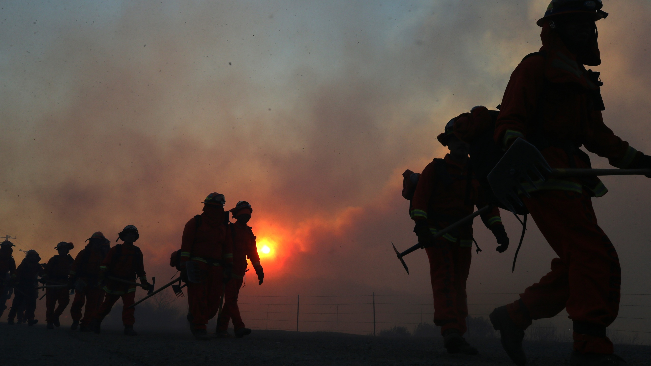 Inmate firefighters work as the Bond Fire burns shortly after sunrise in the Silverado Canyon area of Orange County on December 3, 2020 near Irvine, California. (Photo by Mario Tama/Getty Images)