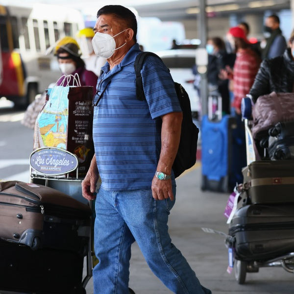 Travelers wait for rides outside the arrivals area of Tom Bradley International Terminal at Los Angeles International Airport (LAX) amid a COVID-19 surge in Southern California on Dec. 22, 2020. (Mario Tama/Getty Images)