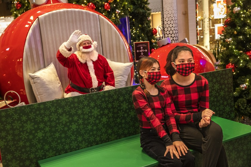 Kelsy Tasem, 11, left, and sister Mackenzi, 14, have their socially distanced photo taken with Santa Claus, played by Jeffrey Fast, during a visit Wednesday to the Westfield Topanga Mall in Canoga Park.(Mel Melcon / Los Angeles Times)