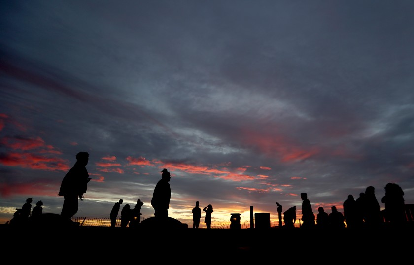 A small crowd takes in the sunset from the top of Signal Hill. Los Angeles County officials are bracing for another COVID-19 surge in early January.(Luis Sinco / Los Angeles Times)