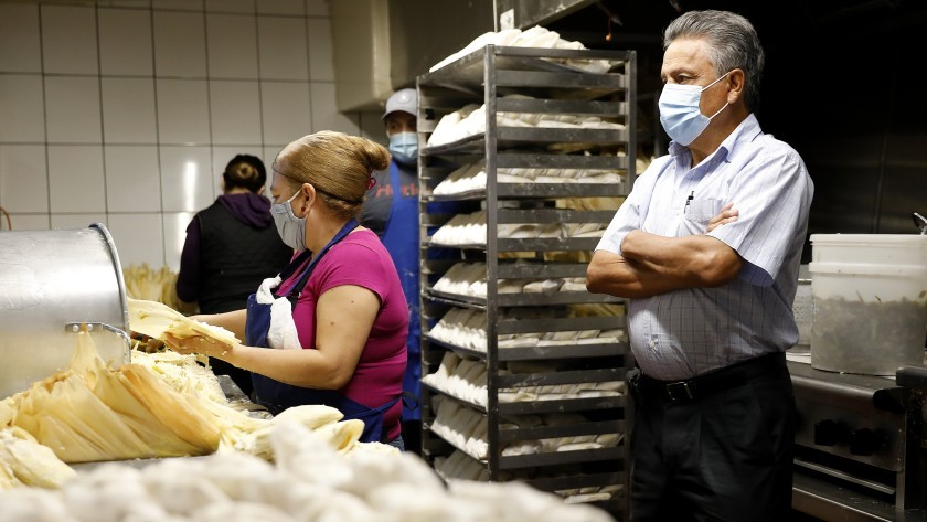 Juan Manuel Santiago, right, looks on as Maria Franco, center, and other workers make tamales at Tamales Liliana's in Los Angeles on Dec. 4. (Christina House / Los Angeles Times)