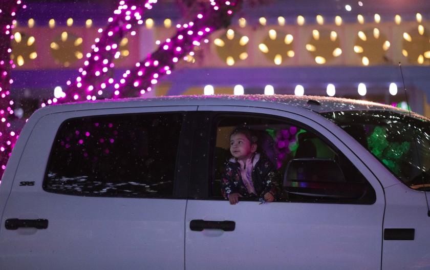 12月3日,在瓦伦西亚的六旗魔山,一名坐在车里的孩子看着假的降雪和五颜六色的灯光。主题公园和其他大型场馆希望灯光秀的入场费能抵消他们在疫情中损失的部分收入。(Myung J. Chun /《洛杉矶时报》)(photo:KTLA)