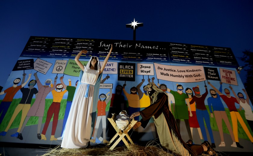 """Claremont United Methodist Church put up a Nativity scene in December 2020 that shows Mary, Joseph and baby Jesus in front of a wall of people wearing masks and carrying signs that read """"Black Lives Matter,"""" """"I can't breathe"""" and """"Jesus wept,"""" along with Bible verses. (Luis Sinco/Los Angeles Times)"""
