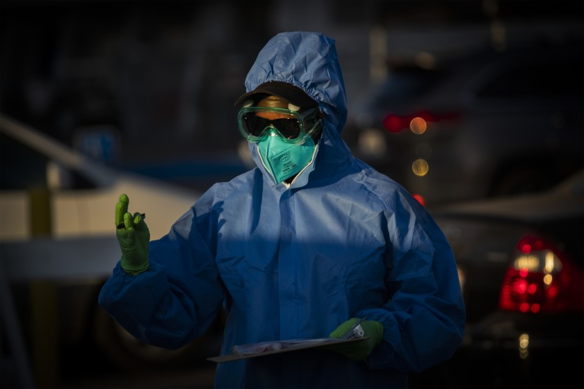 A healthcare worker hands out coronavirus tests at Veterans Memorial Stadium at Long Beach City College on Dec. 9.(Allen J. Schaben / Los Angeles Times)
