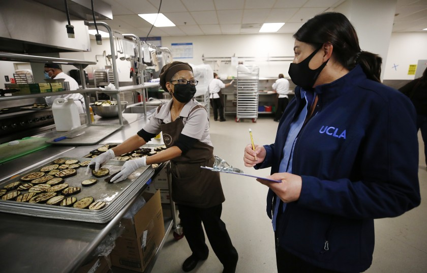 UCLA is grappling with the pandemic's financial fallout in part by redeploying workers, such as those in food service who are now making meals for low-income families as campus demand has plunged. (Al Seib / Los Angeles Times)