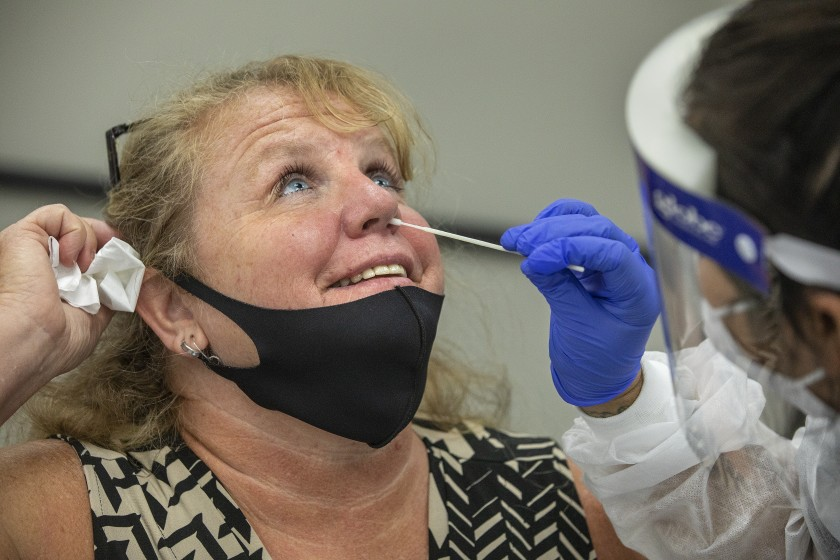 Laurie Goldfinger, left, attendance secretary for Agoura High School, is given a coronavirus test by phlebotomist Jessica Garcia at Wright Middle School in Calabasas.(Mel Melcon / Los Angeles Times)