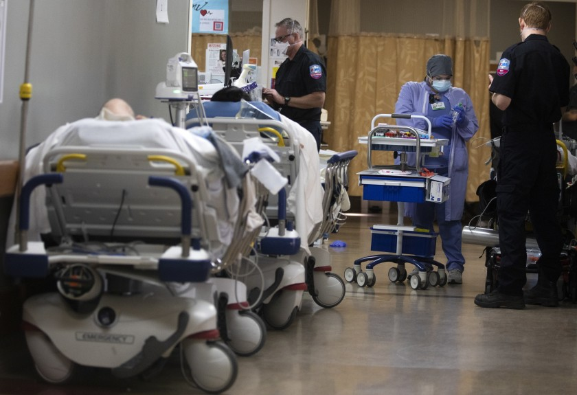 Melissa Quintero takes blood from a patient inside a hallway in the emergency department at Providence St. Mary Medical Center in Apple Valley. The medical center is currently receiving support from the California National Guard. (Francine Orr / Los Angeles Times)