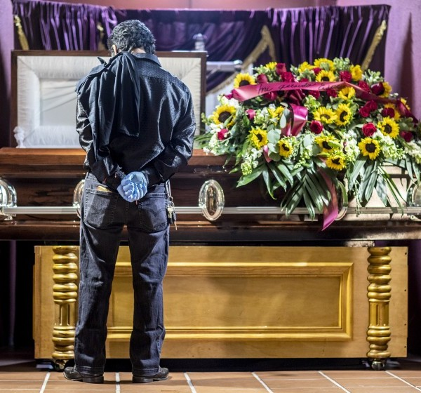 Mario Flores views the body of his godfather, Felipe Juarez, at a funeral service held in August in East Los Angeles. Juarez died of COVID-19. (Robert Gauthier / Los Angeles Times)