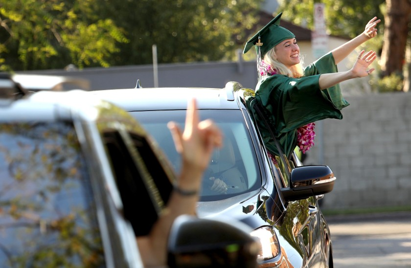 Naomi Shacham waves to her teachers during a drive-up graduation ceremony for the Class of 2020 at the New West Charter School in Los Angeles in June, 2020. (Genaro Molina / Los Angeles Times)