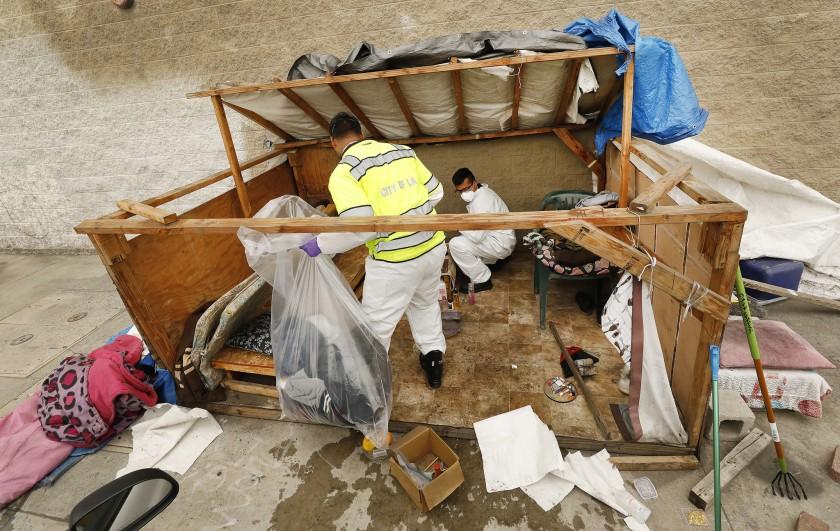 Sanitation workers Jesus Sanchez, left, and Javier Villareal check a homeless encampment for hazardous materials in 2019. (Al Seib / Los Angeles Times)