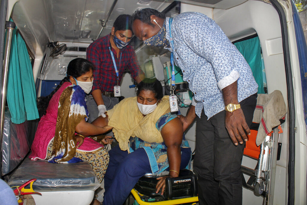 A patient is assisted from an ambulance at the district government hospital in Eluru, Andhra Pradesh state, India, Tuesday, Dec.8, 2020. Health officials and experts are still baffled by a mysterious illness that has left over 500 people hospitalized and one person dead in this southern Indian state. (AP Photo)