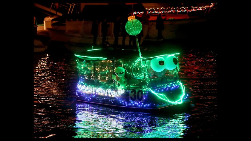 A boat decorated with lights passes by during the Huntington Harbour Boat Parade in 2018. (Raul Roa / Times Community News)
