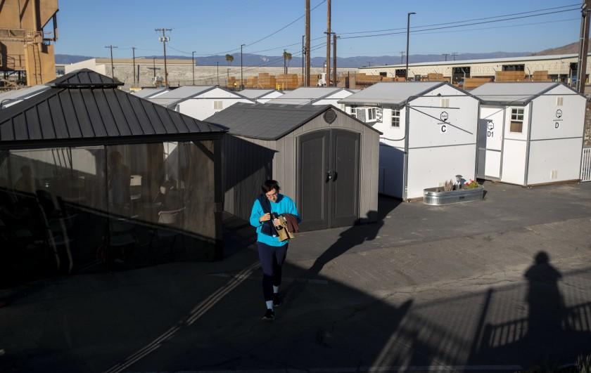 一张未注明日期的照片显示,一个小家村的居民走到公共淋浴区。 (Gina Ferazzi / Los Angeles Times)(photo:KTLA)