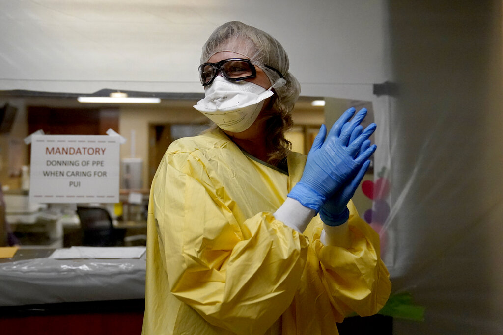 Registered nurse Shelly Girardin prepares to go on rounds after donning personal protective equipment inside an area of Scotland County Hospital sealed off with plastic to care for the influx of COVID-19 patients Tuesday, Nov. 24, 2020, in Memphis, Mo. The coronavirus pandemic is devastating rural hospitals, including the tiny 25-bed facility. (AP Photo/Jeff Roberson)