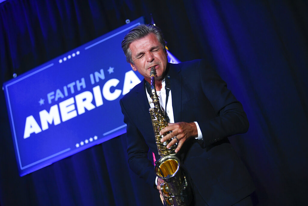 Pastor Jentezen Franklin plays the saxophone during a Trump campaign event courting devout conservatives by combining praise, prayer and patriotism, Thursday, July 23, 2020, in Alpharetta, Ga. (AP Photo/John Amis)