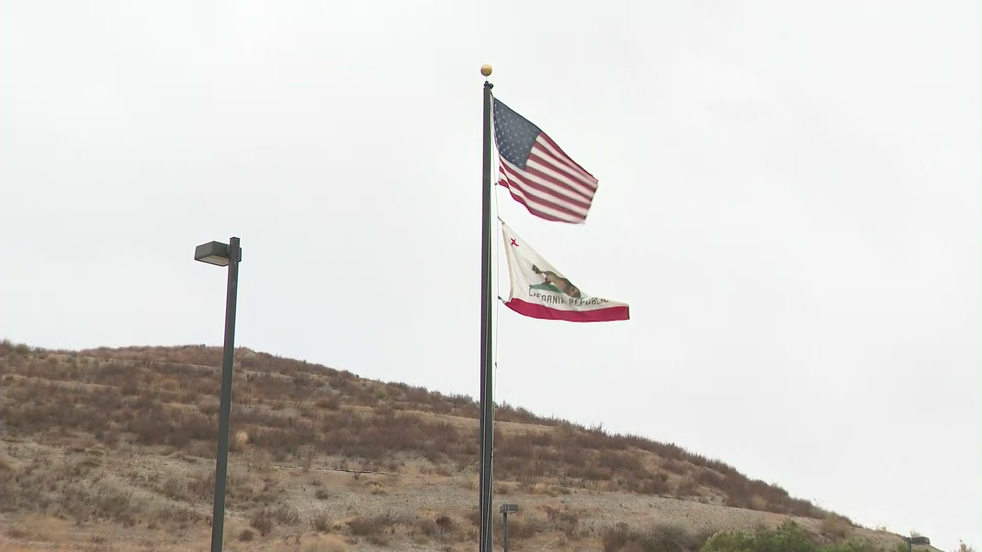 A U.S. and California flag fly in the air as wind blows through Santa Clarita on Dec. 7, 2020. (KTLA)