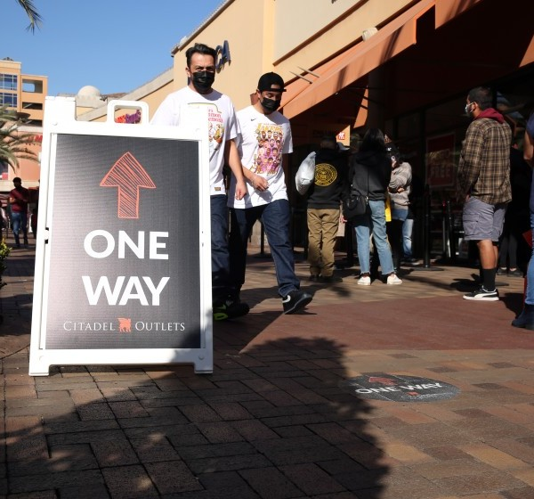 People walk against the suggested flow of foot traffic for coronavirus precautions at the Citadel Outlets in Commerce on Tuesday.(Dania Maxwell / Los Angeles Times)