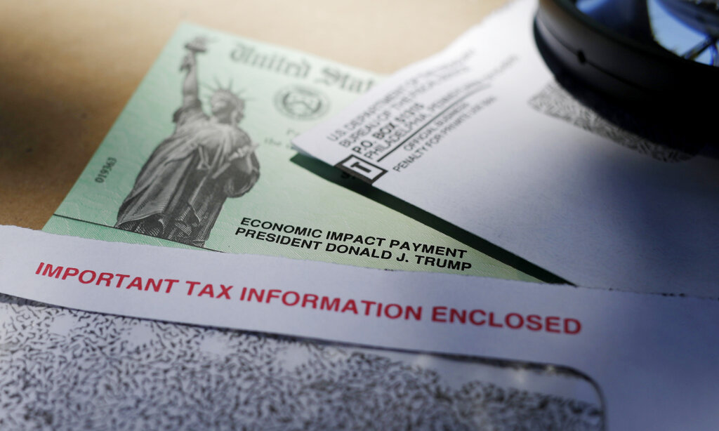 In this April 23, 2020, file photo, President Donald Trump's name is seen on a stimulus check issued by the IRS to help combat the adverse economic effects of the COVID-19 outbreak, in San Antonio. Hundreds of thousands of dollars in coronavirus relief payments have been sent to people behind bars across the United States, and now the IRS is asking state officials to help claw back the cash that the federal tax agency says was mistakenly sent. (AP Photo/Eric Gay, File)