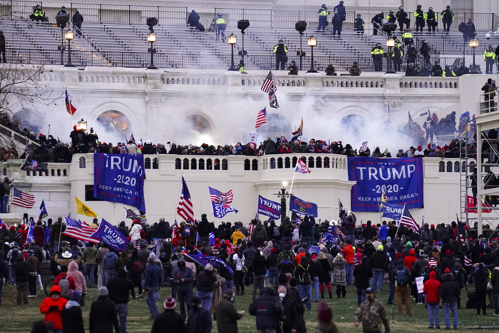 In this Wednesday, Jan. 6, 2021, file photo, violent protesters, loyal to President Donald Trump, storm the Capitol, in Washington. Federal prosecutors say a retired Air Force officer who was part of the mob that stormed the U.S. Capitol was arrested Sunday, Jan. 10, 2021, in Texas. (AP Photo/John Minchillo, File)
