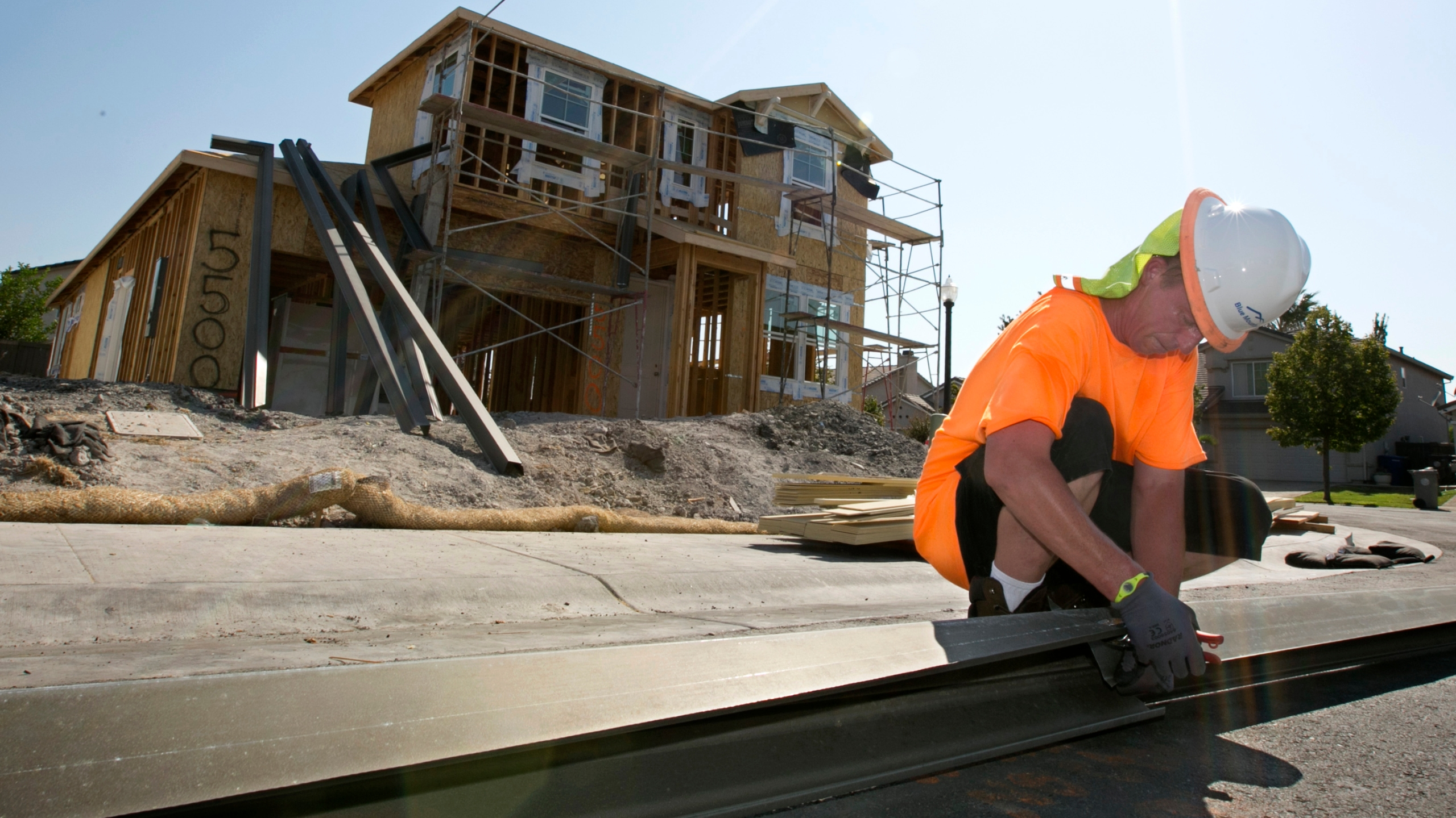 In this photo taken Aug. 16, 2017, sheet metal worker Benjamin Voget prepares to install a gutter on a home under construction in Sacramento. (Rich Pedroncelli / Associated Press)
