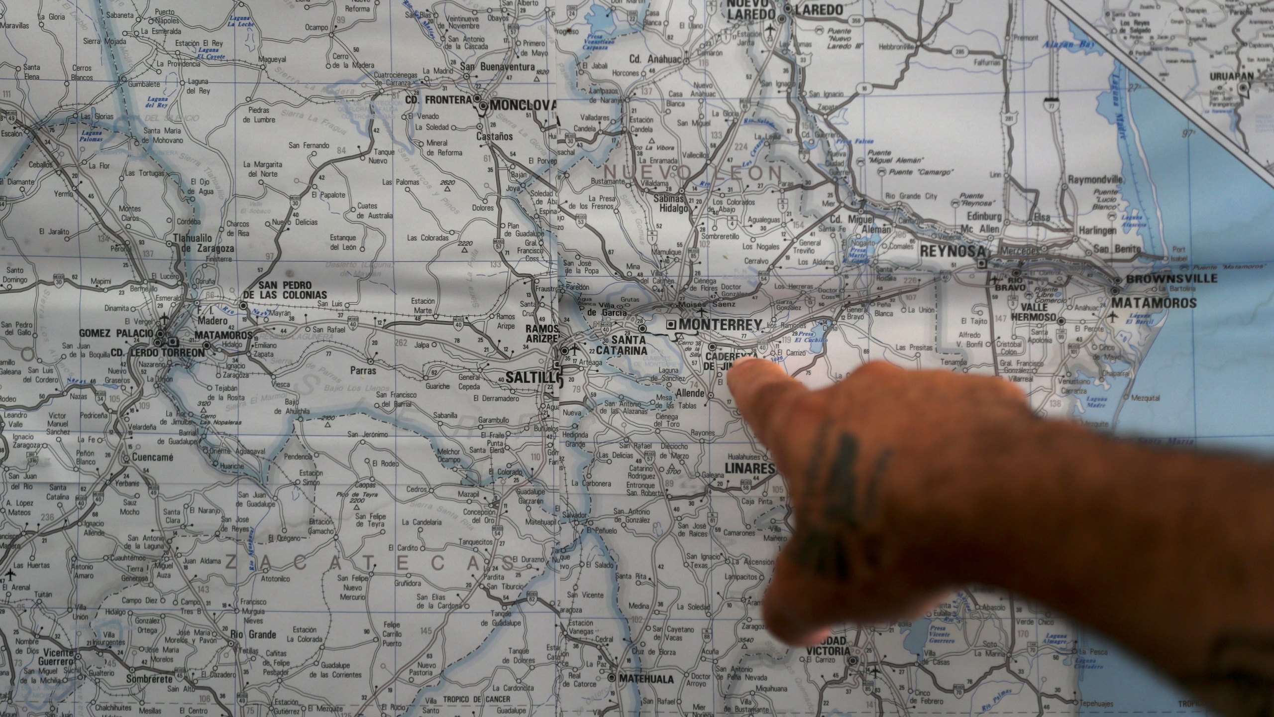 In this Oct. 10, 2019 photo, a Mexican migrant points to a map of U.S.-Mexico border cities, hanging on display at a migrant shelter in Reynosa, Mexico. The Mexican state of Tamaulipas used to be a crossroads. Its dangers are well known. (AP Photo/Fernando Llano)