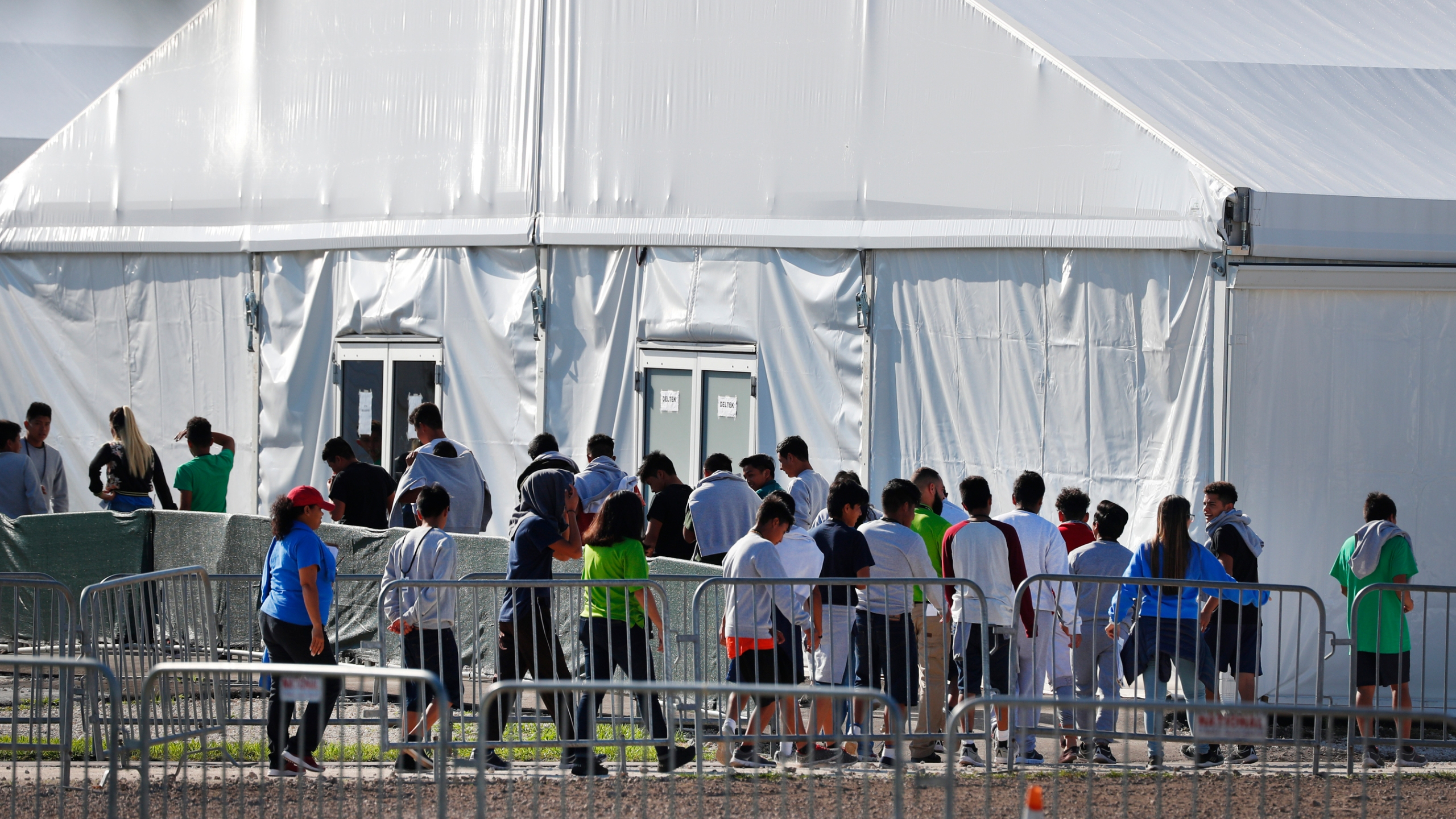 In this Feb. 19, 2019, file photo, children line up to enter a tent at the Homestead Temporary Shelter for Unaccompanied Children in Homestead, Fla. (Wilfredo Lee/Associated Press)