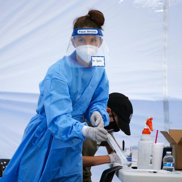 In this file photo, Dr. Sabrina Solt prepares an appointment-only coronavirus drive-thru swab test in the parking lot at Impact Church, Monday, May 4, 2020, in Scottsdale, Ariz. The 2-day testing site for both the coronavirus and the antibody test was made possible by a partnership with Arizona Cardinals' NFL football player Jordan Hicks and Impact Church, hoping to test 500 people. (AP Photo/Ross D. Franklin)