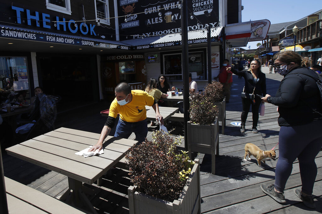 In this June 18, 2020, file photo, a man wears a face mask while cleaning an outdoor dining table at The Hook at Pier 39 in San Francisco. (AP Photo/Jeff Chiu, File)