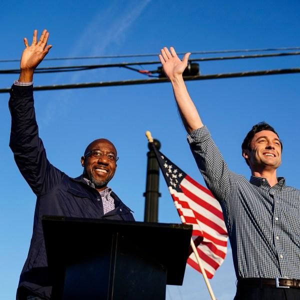 Then Georgia Democratic candidates for U.S. Senate Raphael Warnock, left, and Jon Ossoff, right, gesture toward a crowd during a campaign rally on Nov. 15, 2020, in Marietta, Ga. (Brynn Anderson/Associated Press)